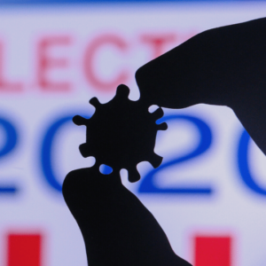 """Coronavirus held between thumb and forefinger, with """"election 2020"""" in the background"""